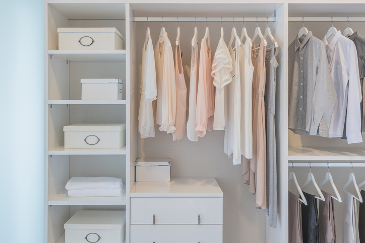 Image of clothes hanging on rail in white wardrobe with boxes