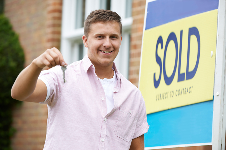 Young man holding keys to new home