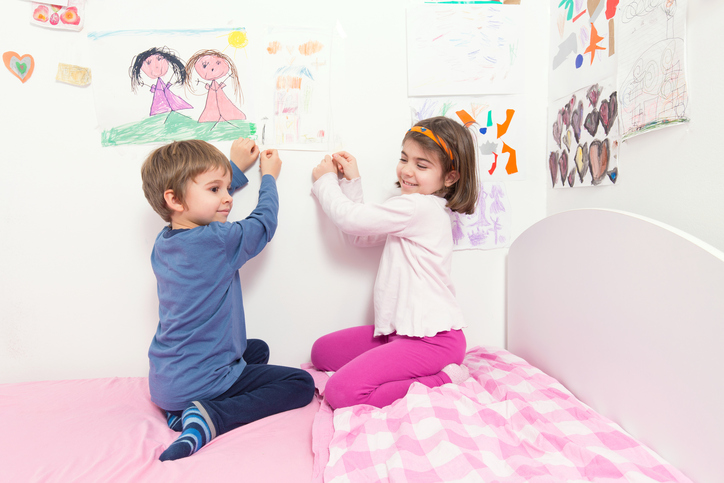 Image of children setting their drawings on the wall of their room