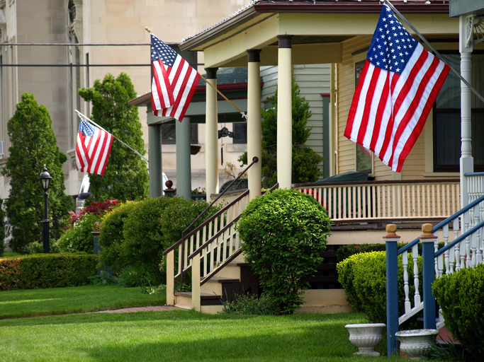 Image of American flags flying from front porches