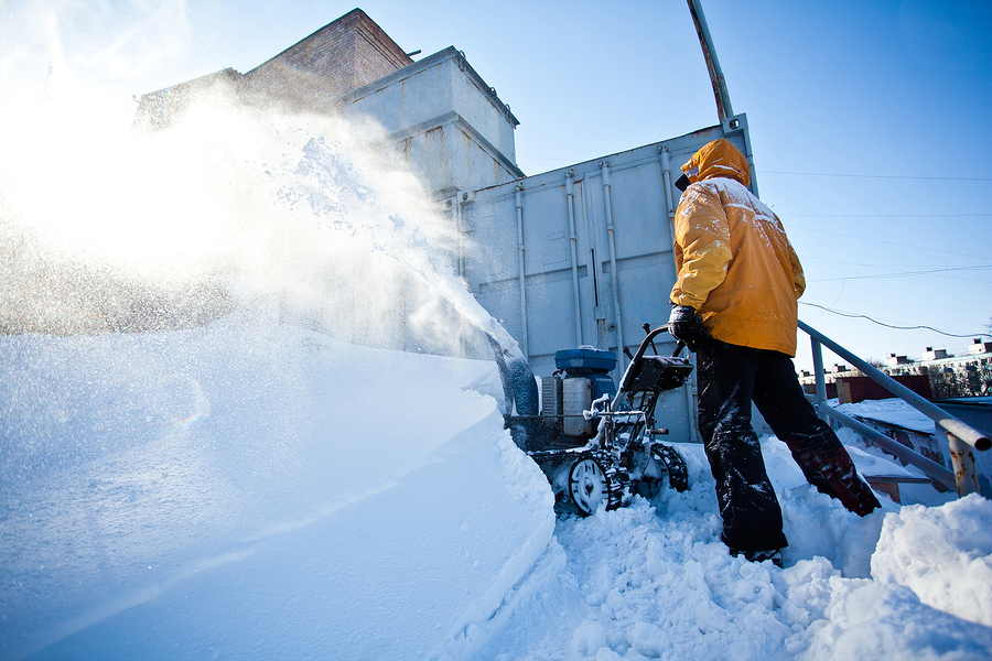 Worker in yellow winter jacket removes snow near his garage with a snow throwing machine at a sunny winter day. Clouds of snow dust around. Seasonal photo