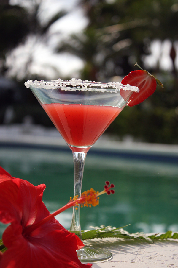strawberry margarita at the edge of the pool with red hibiscus flower taken in Miami