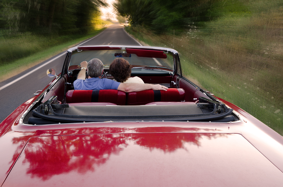 A middle-aged couple snuggle together as they zoom down a county road in a classic red convertible perhaps on a Sunday drive as they enjoy the experience and each other's company.