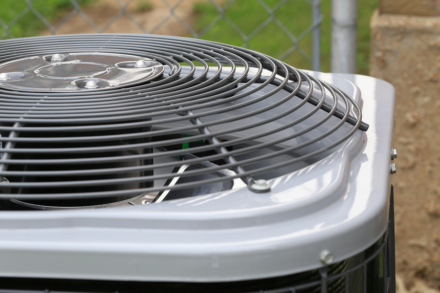 Picture of a brand new air conditioner, installed at a residential home. Shows top grill and fan blades