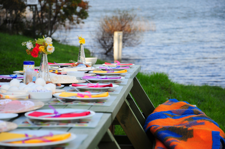 colorful picnic table on grass by sea (lake/river) in spring