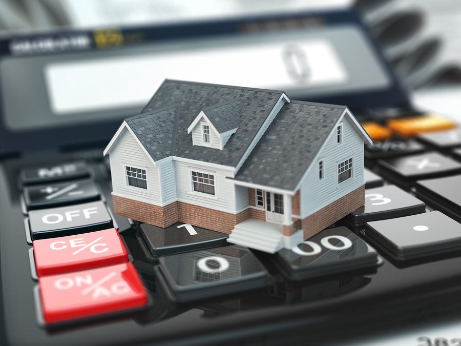 Image of house on top of calculator to symbolize financial oligations