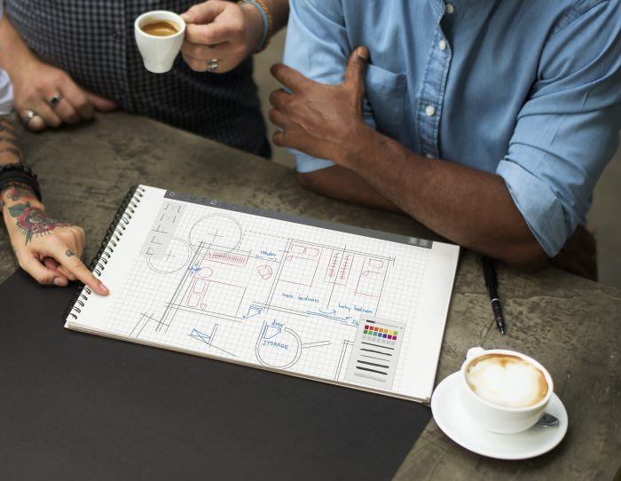 Three people reviewing a floor plan