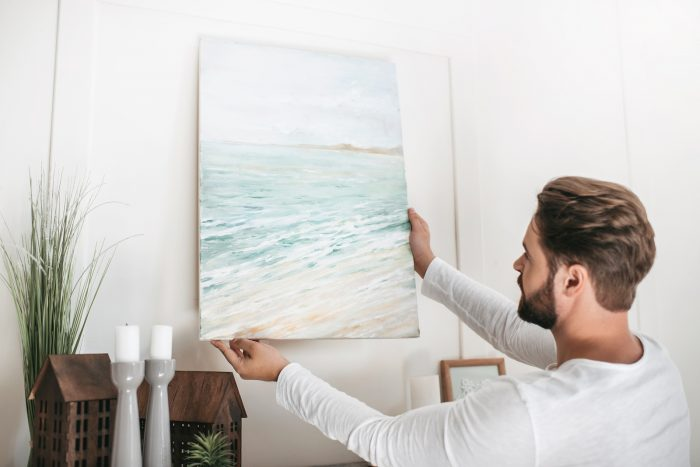 Young bearded man hanging picture on wall at home