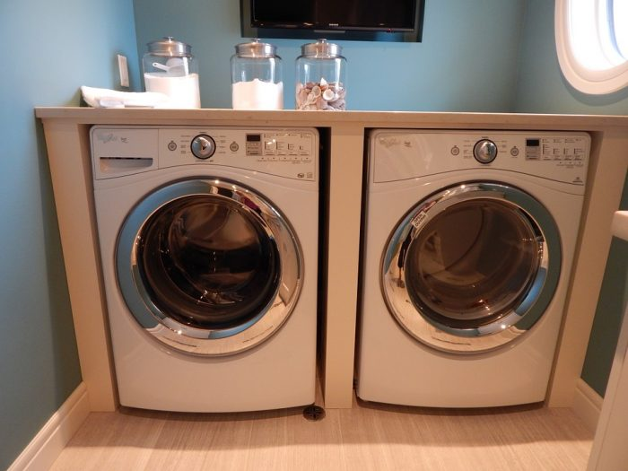 A white and stainless steel washer and dryer set in a laundry room.
