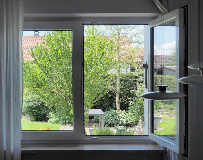 An open window leading to a beautiful garden view.