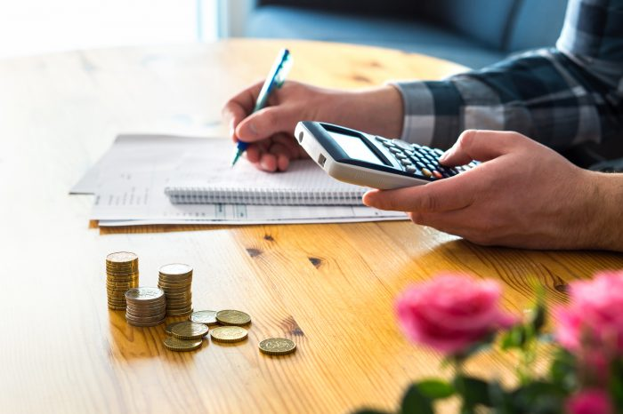 Man using calculator and counting budget, expenses and savings.